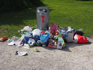 garbage can surrounded with rubbish